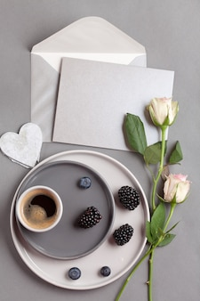 Draufsicht über kaffeetasse und graue postkarte mit umschlag