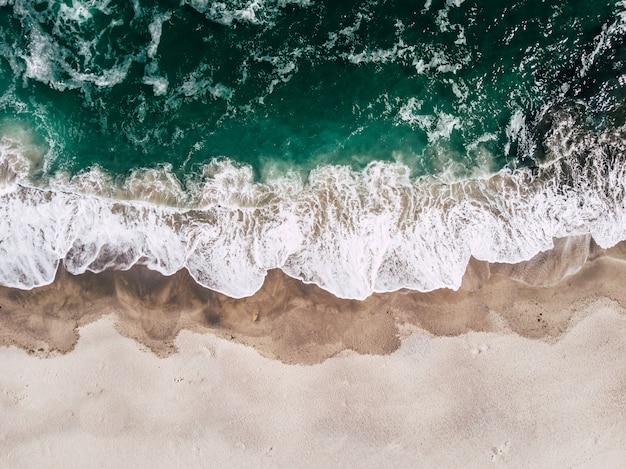 Draufsicht über spritzen von meer, von schönem strand und von meer vom luftbrummen