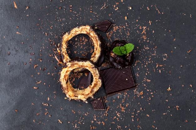 Draufsicht über stücke eines schokoladenkuchens und der schokolade mit tadellosem blatt auf einem dunklen hintergrund