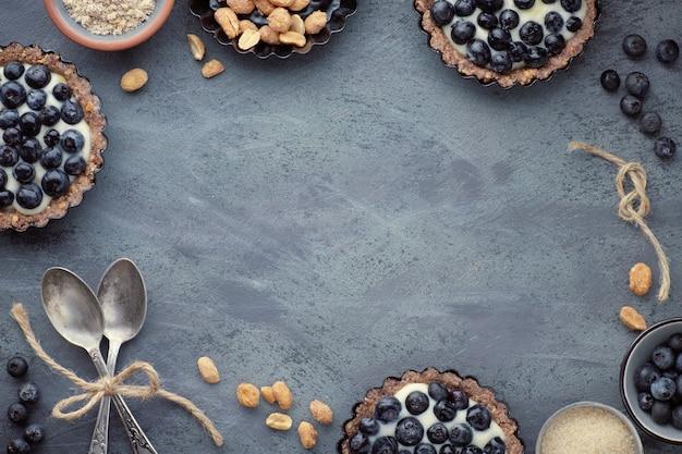 Draufsicht über vollkornblaubeertörtchen mit vanillecreme auf dunklem hintergrund
