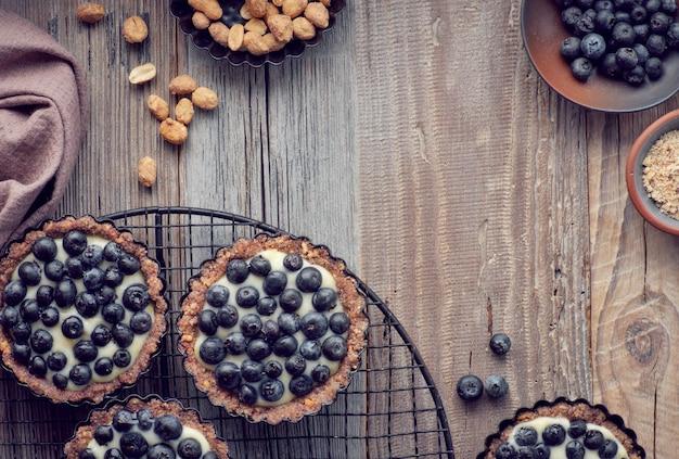 Draufsicht über vollkornblaubeertörtchen mit vanillecreme auf rustikalem holz