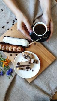 Draufsicht über weibliche hände mit sommerblumen nahe einer schale schwarzem kaffee und gedienten eclairs