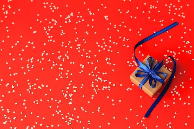 Draufsicht über weihnachtsgeschenke mit band auf rotem papierhintergrund mit silbernen sternen. copyspace.