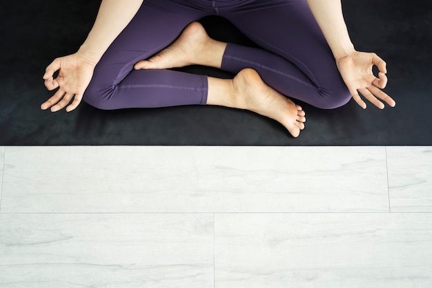 Draufsicht und nahaufnahmefoto von den leuten, die ein yoga in der turnhalle aufwerfen
