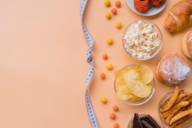 Draufsicht ungesunde snacks und maßband mit kopierraum