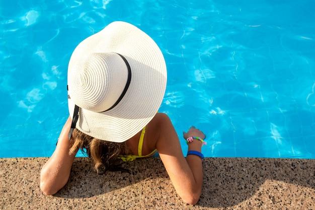 Draufsicht unten der jungen frau, die gelben strohhut trägt, der im schwimmbad mit klarem blauem wasser am sonnigen sommertag ruht.