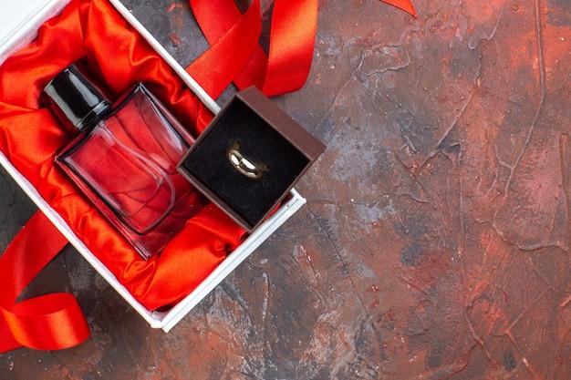 Draufsicht valentinstag geschenk duft auf dunkler oberfläche geschenk parfüm liebe farbe paar frau ring ehe
