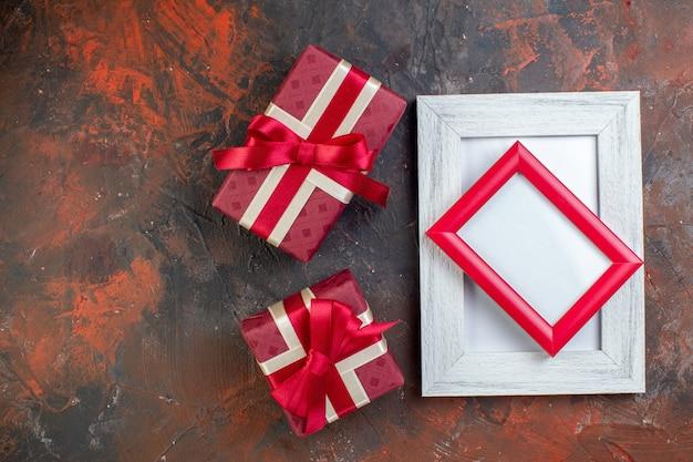 Draufsicht valentinstag präsentiert mit bilderrahmen auf dunklem hintergrund fotogeschenk geschenk farbe liebesgefühl ich liebe dich