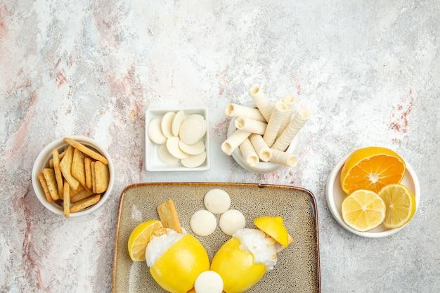Draufsicht vereiste zitronen mit bonbons und crackern auf weißem tisch
