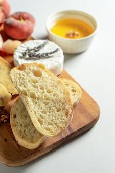Draufsicht verschiedene arten von käse auf holzschneidebrett. käse mit feigenpfirsich, honig, ciabatta und nüssen, glas rotwein. stilvolle lebensmittelwohnung lag auf grauem hintergrund. speicherplatz kopieren. weicher fokus