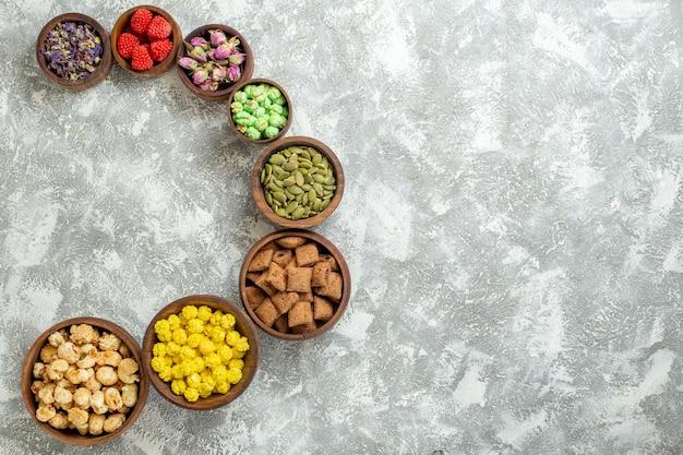 Draufsicht verschiedene bonbons mit nüssen auf weißer oberfläche süßigkeiten tee zuckerkuchen viele