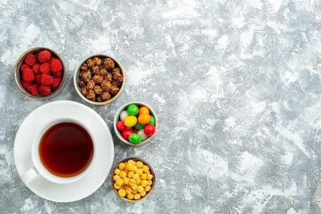 Draufsicht verschiedene bonbons mit nüssen und tasse tee auf leerraum