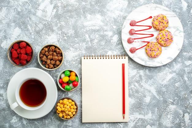 Draufsicht verschiedene bonbons mit nusskeksen und tasse tee auf weißem raum