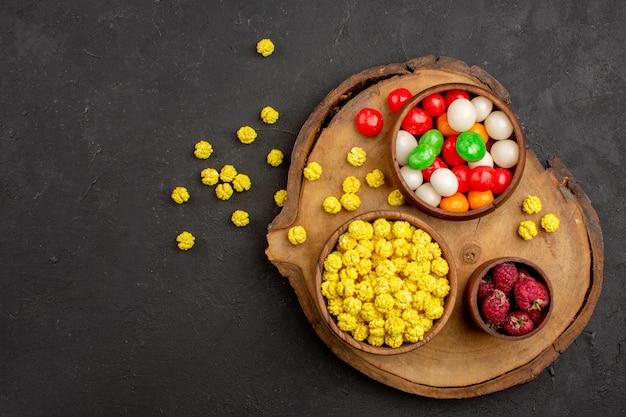 Draufsicht verschiedene bunte bonbons auf dem dunklen schreibtisch bonbonfarben regenbogen-zuckertee