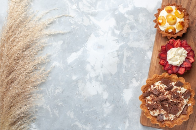 Draufsicht verschiedene cremige kuchen mit schokolade und früchten auf dem weißen schreibtischkuchen backen keks süße zuckerfrucht