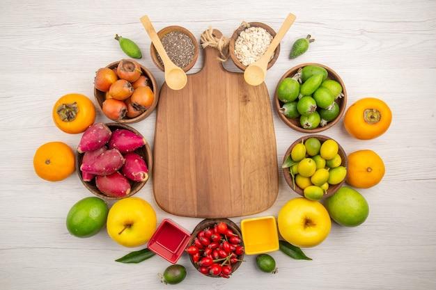 Draufsicht verschiedene frische früchte in platten auf dem weißen hintergrund tropische reife farbdiät mildes exotisches gesundes leben