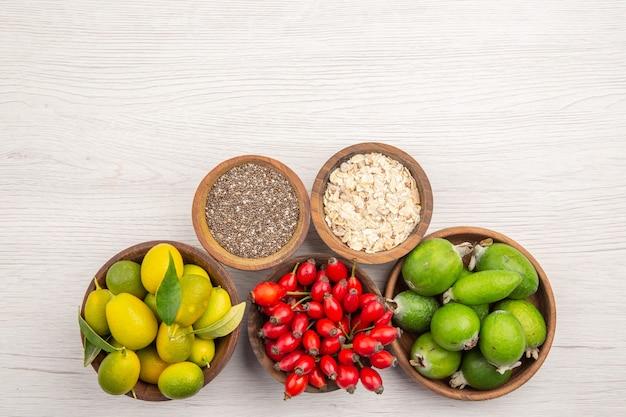 Draufsicht verschiedene frische früchte in platten auf weißem hintergrund exotische reife gesunde leben tropische farbe
