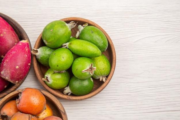 Draufsicht verschiedene frische früchte in platten auf weißem hintergrund exotische tropische reife ernährung farbe gesundes leben
