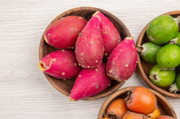 Draufsicht verschiedene frische früchte in platten auf weißem hintergrund obst tropische ernährung exotische farbe gesundes leben