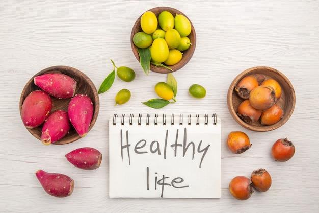 Draufsicht verschiedene frische früchte in platten auf weißem hintergrund obst tropische reife ernährung exotische farbe gesundes leben