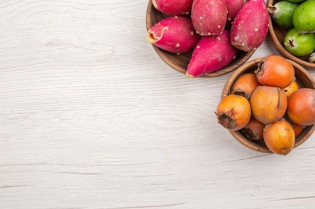 Draufsicht verschiedene frische früchte in platten auf weißem hintergrund obst tropische reife ernährung exotisches gesundes leben