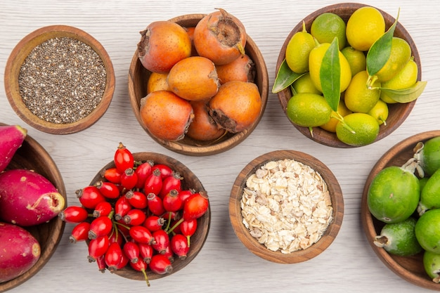 Draufsicht verschiedene frische früchte in platten auf weißem hintergrund reife exotische gesunde lebensfarbendiät
