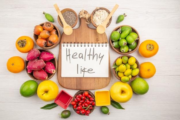 Draufsicht verschiedene frische früchte in platten auf weißem hintergrund reife farbe diät mildes exotisches gesundes leben