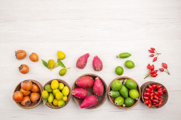 Draufsicht verschiedene frische früchte in platten auf weißem hintergrund tropische reife ernährung farbe gesundes leben