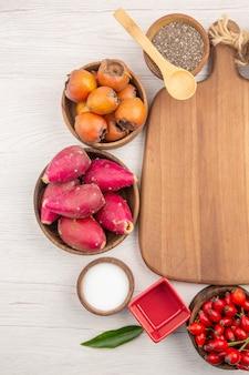 Draufsicht verschiedene frische früchte in platten auf weißem hintergrund tropische reife farbdiät exotisches gesundes leben