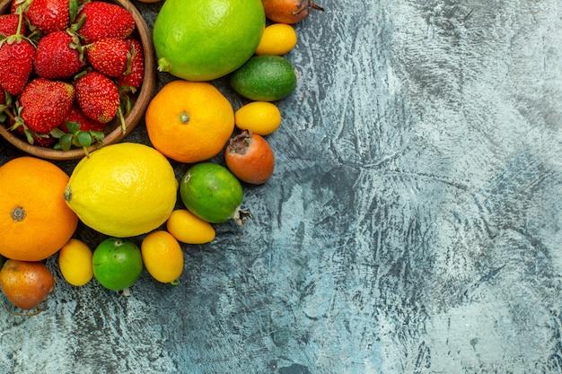Draufsicht verschiedene frische früchte mit roten erdbeeren auf grauem hintergrund