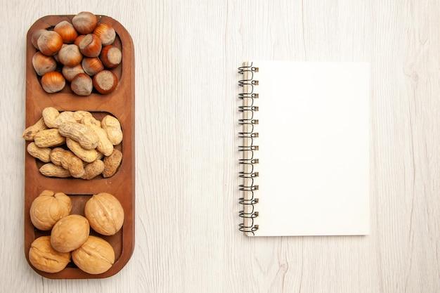 Draufsicht verschiedene frische nüsse erdnüsse haselnüsse und walnüsse auf weißem schreibtisch nuss snack viele pflanzen