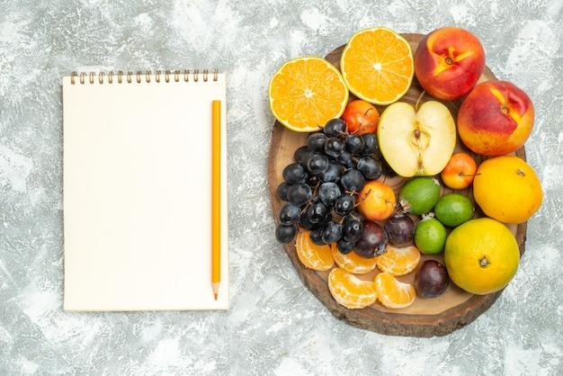 Draufsicht verschiedene fruchtzusammensetzung in scheiben geschnitten und ganze frische früchte auf weißem hintergrund baum vitamin reife frucht reife farbe
