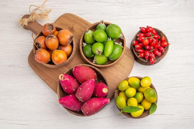 Draufsicht verschiedene früchte feijoas beeren und andere früchte in tellern auf weißem hintergrund reifes essen exotische farbe