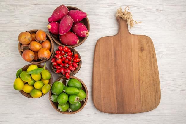 Draufsicht verschiedene früchte feijoas und andere früchte in platten auf weißem hintergrund farbe tropische gesundheit exotischer beerenbaum reif