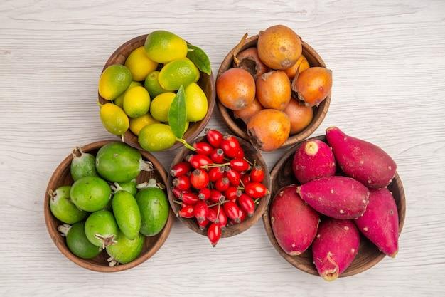 Draufsicht verschiedene früchte feijoas und andere früchte in platten auf weißem hintergrund gesundheit reife exotische tropische baumbeere farbe