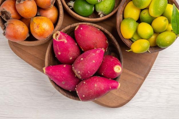 Draufsicht verschiedene früchte feijoas und andere früchte in tellern auf weißem hintergrund reifes essen exotische farbe