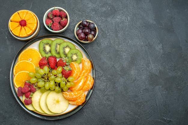 Draufsicht verschiedene früchte zusammensetzung frische und geschnittene früchte auf dem dunklen hintergrund gesundheit reife frische früchte mellow