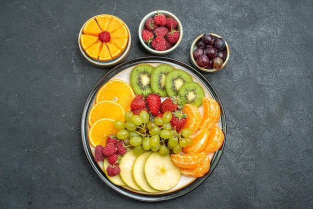 Draufsicht verschiedene früchte zusammensetzung frische und geschnittene früchte auf dunklem hintergrund gesundheit reife frische früchte ausgereift