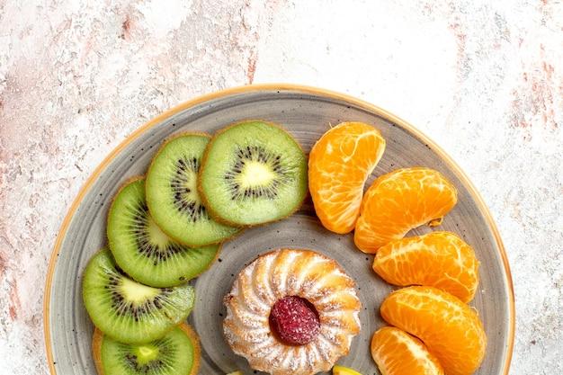 Draufsicht verschiedene früchte zusammensetzung frische und geschnittene früchte mit kuchen auf hellweißem hintergrund ausgereifte reife früchte farbe gesundheit