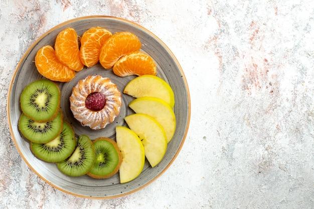 Draufsicht verschiedene früchte zusammensetzung frische und geschnittene früchte mit kuchen auf weißem hintergrund ausgereifte reife früchte farbe gesundheit