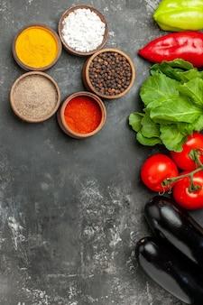 Draufsicht verschiedene gewürze in kleinen schüsseln tomaten paprika auberginen grüns auf grauem hintergrund