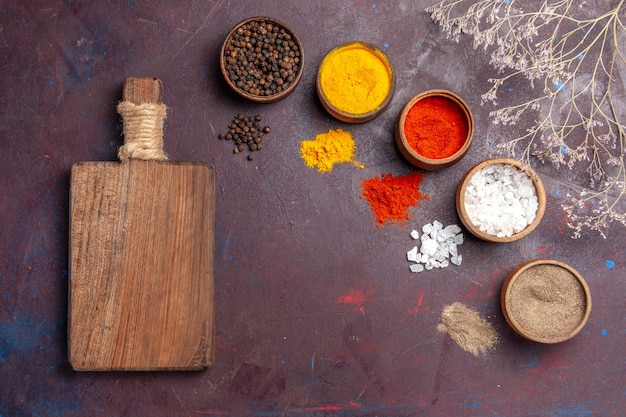 Draufsicht verschiedene gewürze in töpfen auf dem dunklen hintergrund suppensauce mahlzeit würziges pfeffernahrung