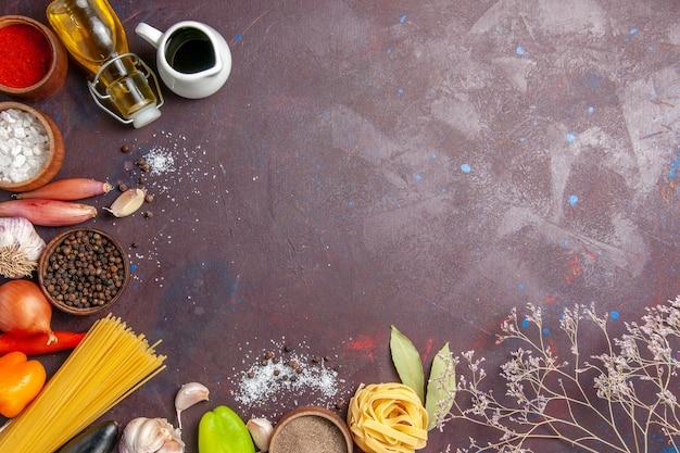Draufsicht verschiedene gewürze mit frischem gemüse auf dem dunklen hintergrund würzigen pfeffernahrungssalatgesundheit