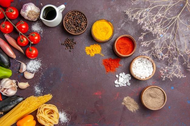 Draufsicht verschiedene gewürze mit gemüse auf dunklem hintergrund suppensauce mahlzeit würziges pfeffernahrung