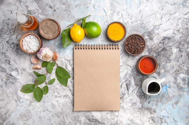 Draufsicht verschiedene gewürze mit zitrone und knoblauch auf weißem tafelöl würziges fruchtsalz