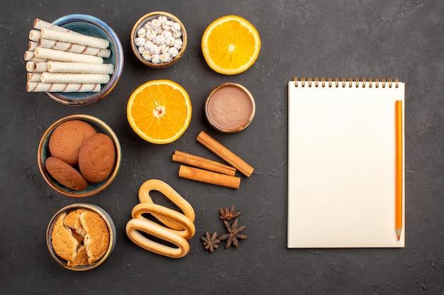 Draufsicht verschiedene kekse mit geschnittenen orangen auf dunklem hintergrund zucker tee keks keks süße frucht