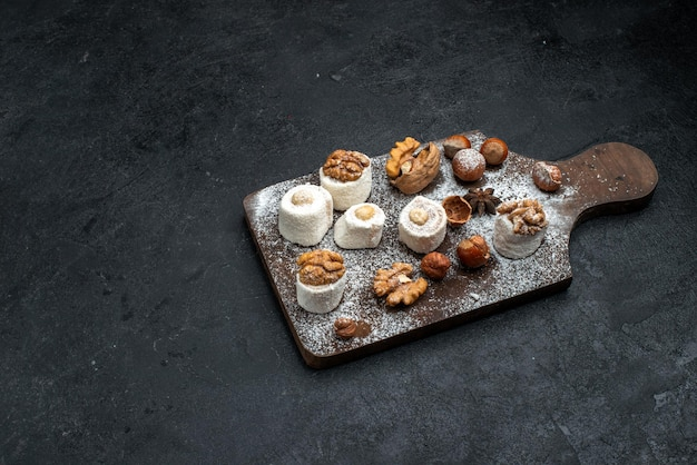 Draufsicht verschiedene kekse mit kuchen und walnüssen auf der dunkelgrauen oberfläche