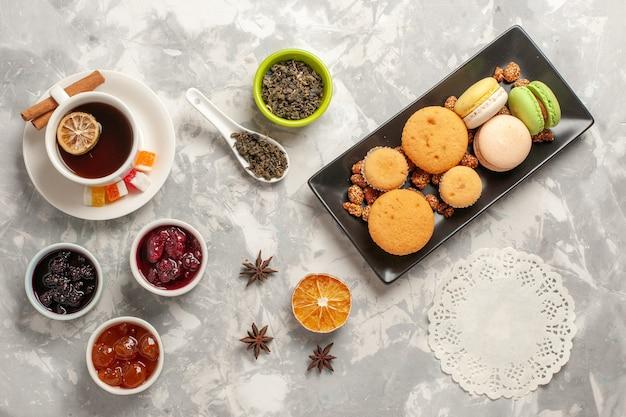 Draufsicht verschiedene kekse mit marmeladen und tasse tee auf dem weißen schreibtischkekszuckerkuchenkuchen süße kekse