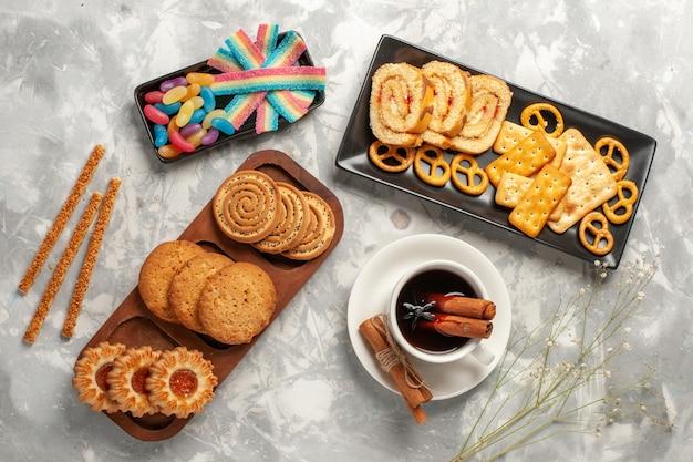 Draufsicht verschiedene kekse mit süßigkeiten und tasse tee auf weißer oberfläche kekse kekszucker backen kuchen süße torte