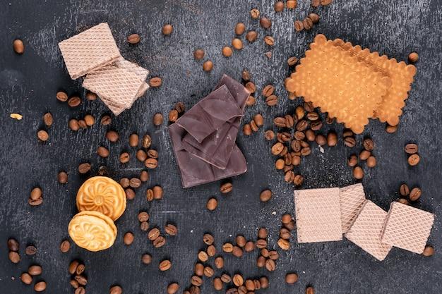 Draufsicht verschiedene kekse schokolade und kaffeebohnen auf dunkler oberfläche